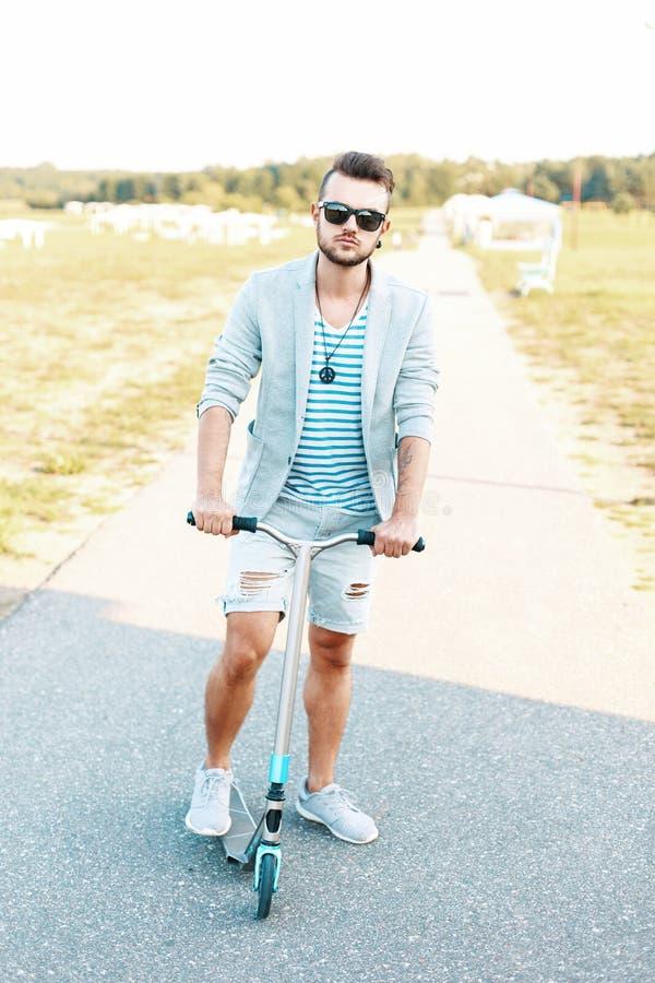 Knappe jonge hipsterkerel in een modieus jasje in gescheurde borrels stock foto's