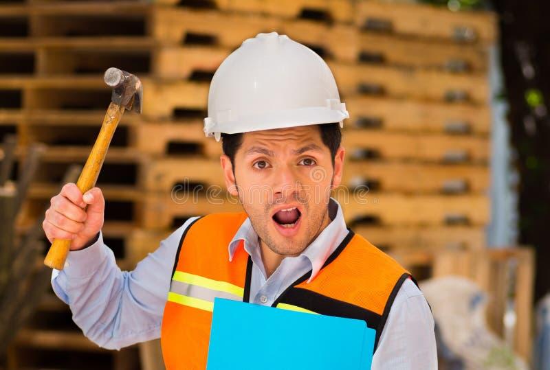 Knappe jonge ingenieur die een omslag en een hamer in zijn hand houden bij bouwwerf die gek worden stock afbeelding