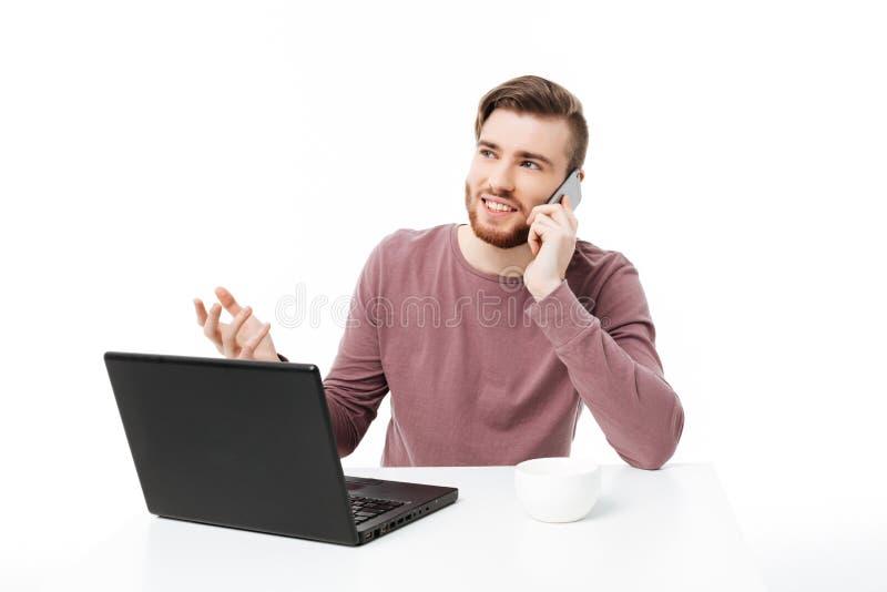 Knappe jonge kerel die bij de laptop computer die aan de telefoon werken en omhoog met open geïsoleerd handgebaar kijken spreken royalty-vrije stock afbeeldingen