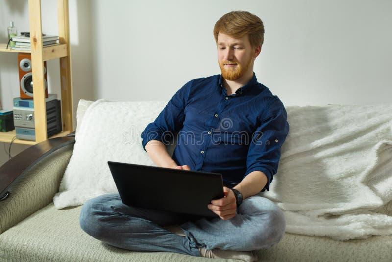 Knappe jonge kerel met een baard die thuis met laptop werken stock afbeeldingen