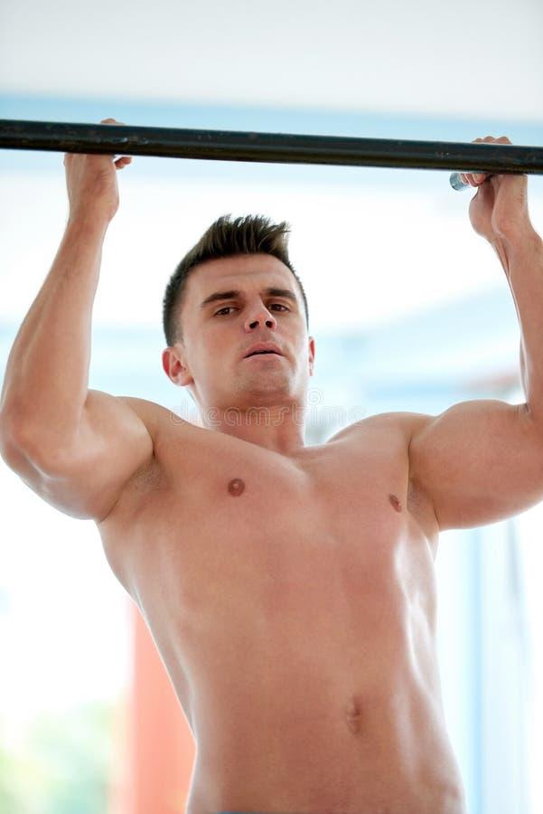 Knappe jonge mand die in gymnastiek uitwerken stock foto's