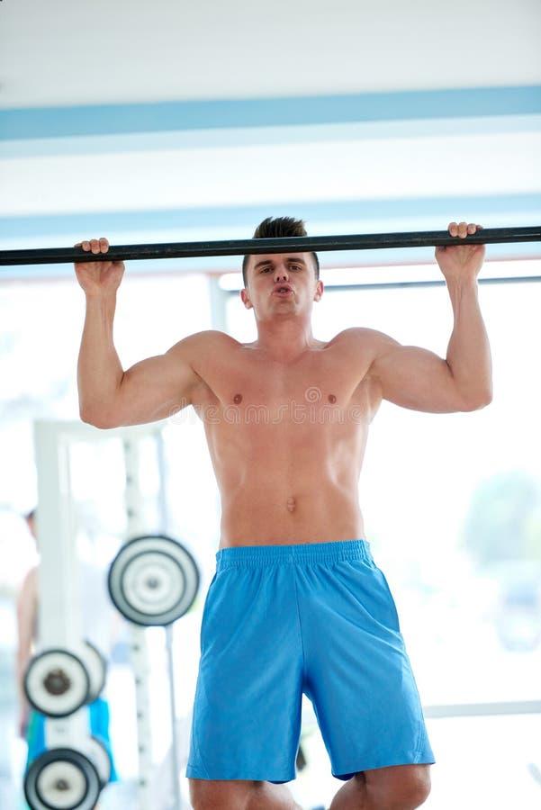Knappe jonge mand die in gymnastiek uitwerken stock foto