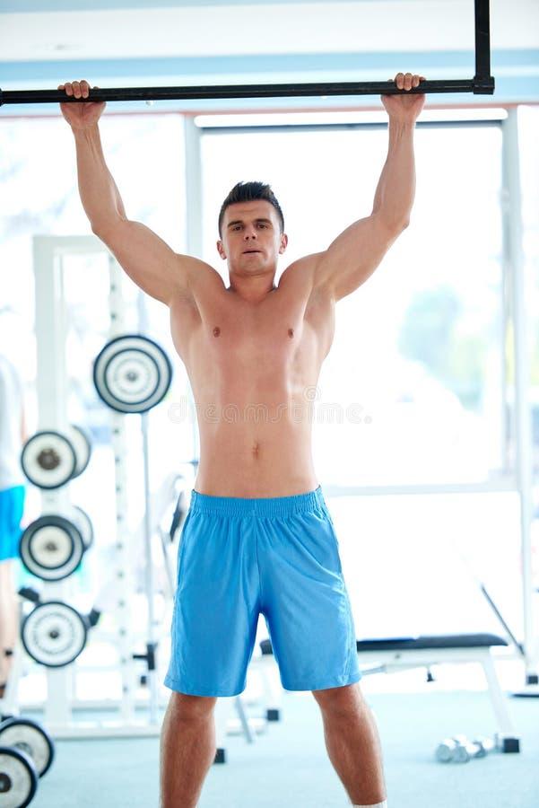 Knappe jonge mand die in gymnastiek uitwerken royalty-vrije stock foto