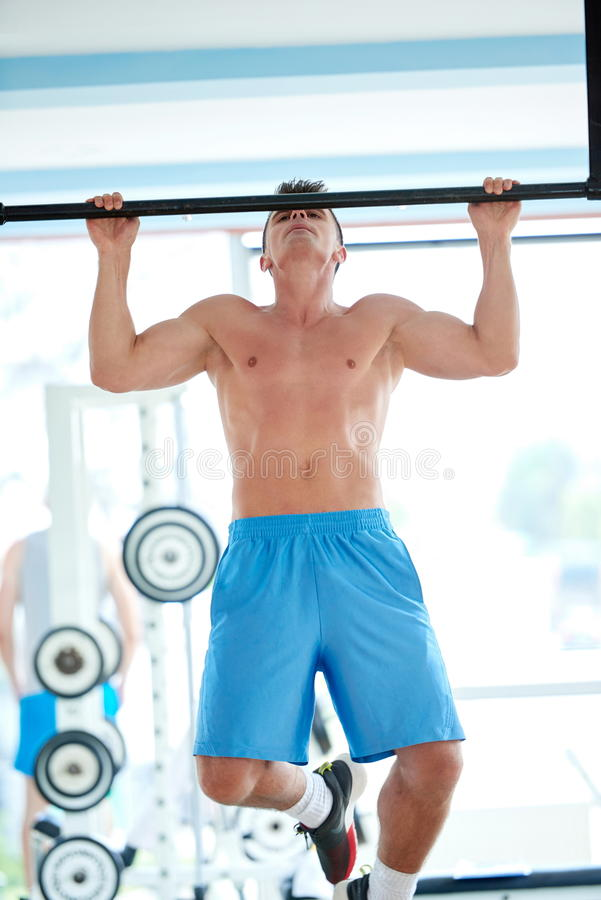 Knappe jonge mand die in gymnastiek uitwerken stock afbeelding
