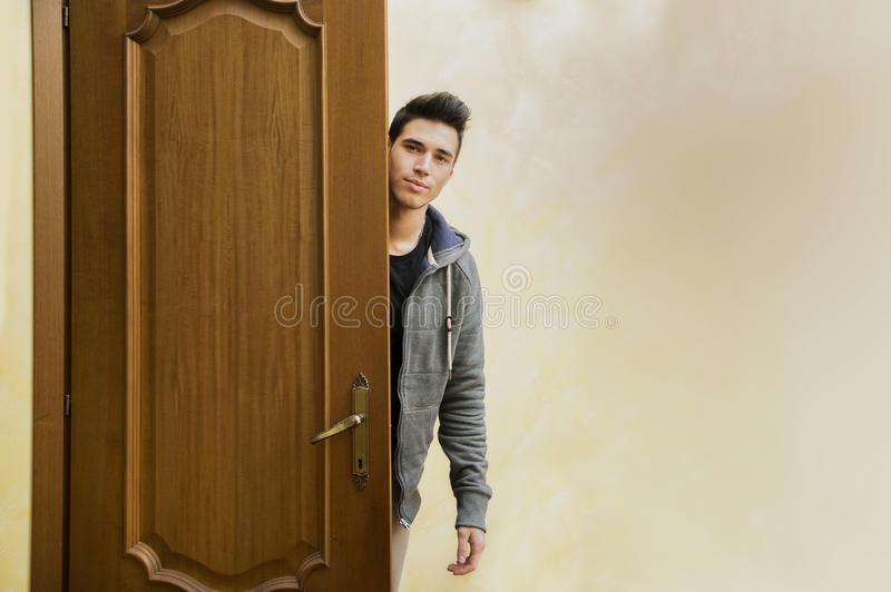 Knappe jonge mens achter open deur, die weggaan stock fotografie