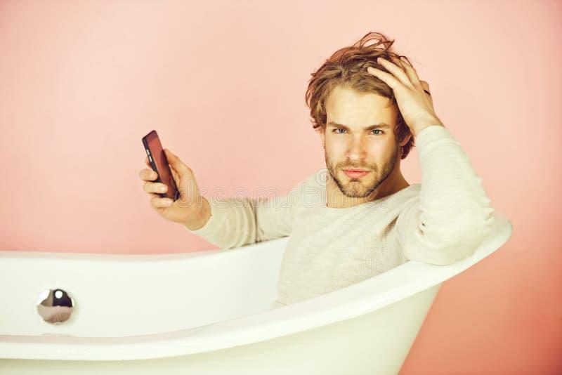 knappe jonge mens in badkuip met mobiele telefoon royalty-vrije stock foto's