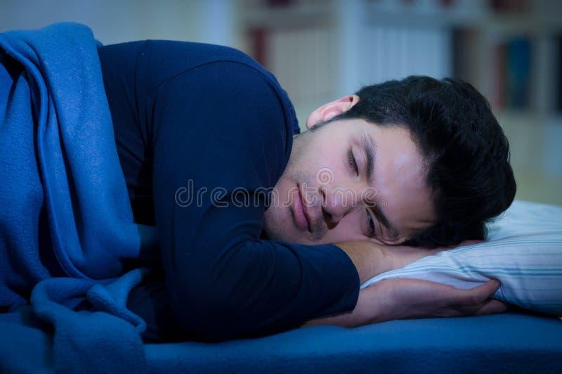 Knappe jonge mens in bed die in slaap na het lijden van slapeloosheid en slaap aan wanorde vallen stock afbeelding