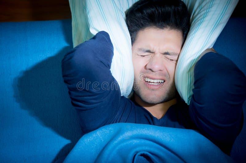 Knappe jonge mens in bed die slapeloosheid en slaap aan wanorde lijden, die zijn oren behandelen met een hoofdkussen, boven menin royalty-vrije stock afbeelding