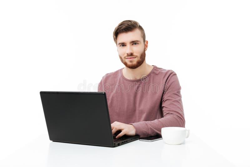 Knappe jonge mens bij de lijst die in de camera die de laptop geïsoleerde computer bekijken werken stock foto's