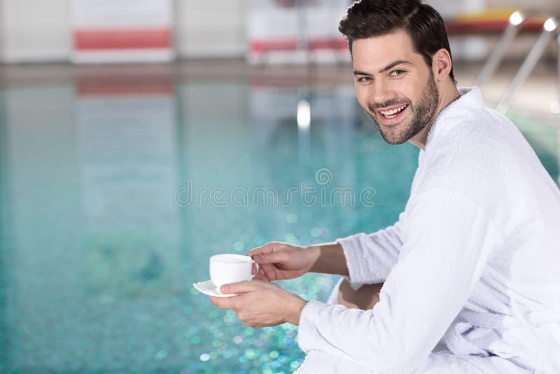 knappe jonge mens in de kop van de badjasholding van koffie en het glimlachen bij camera royalty-vrije stock afbeeldingen