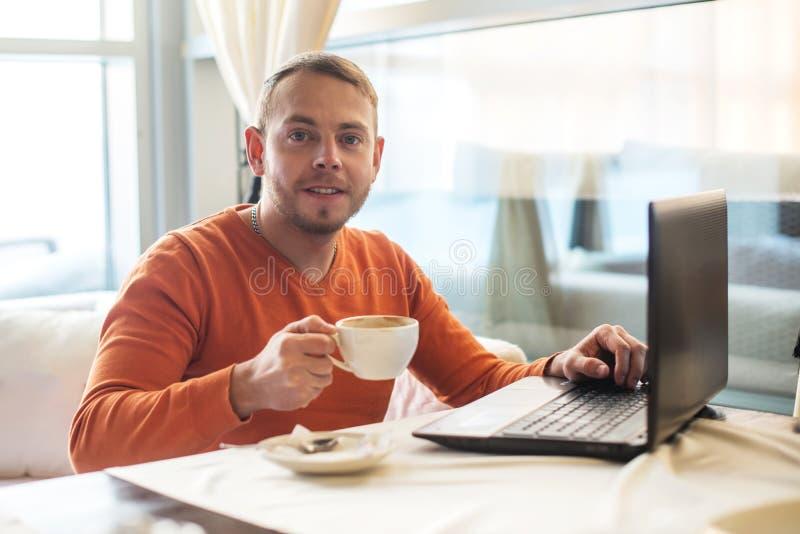 Knappe jonge mens die aan notitieboekje, het glimlachen werken, die camera bekijken, terwijl het genieten van van koffie in koffi stock fotografie