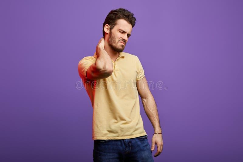 Knappe jonge mens die aan strenge, verlengde halspijn lijden stock afbeeldingen