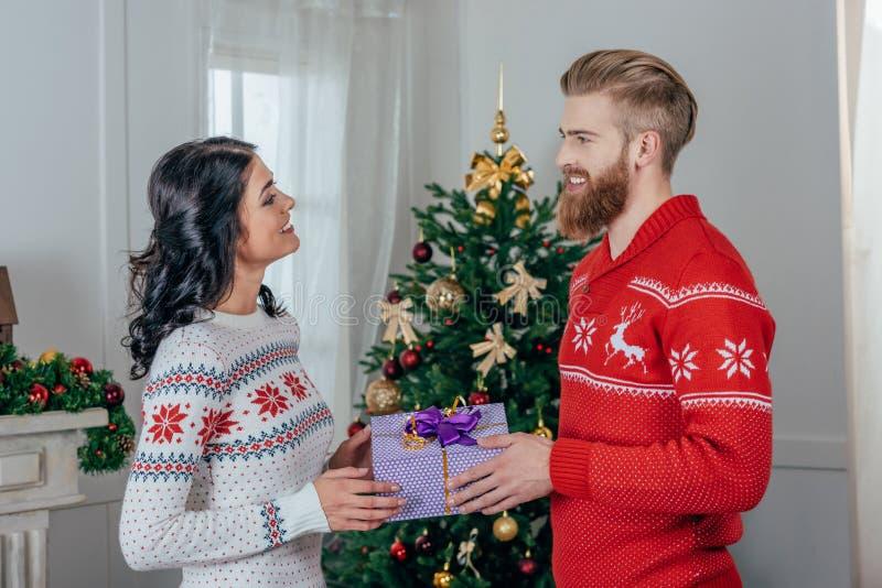 knappe jonge mens die aanwezige Kerstmis geven aan zijn mooi meisje royalty-vrije stock afbeelding