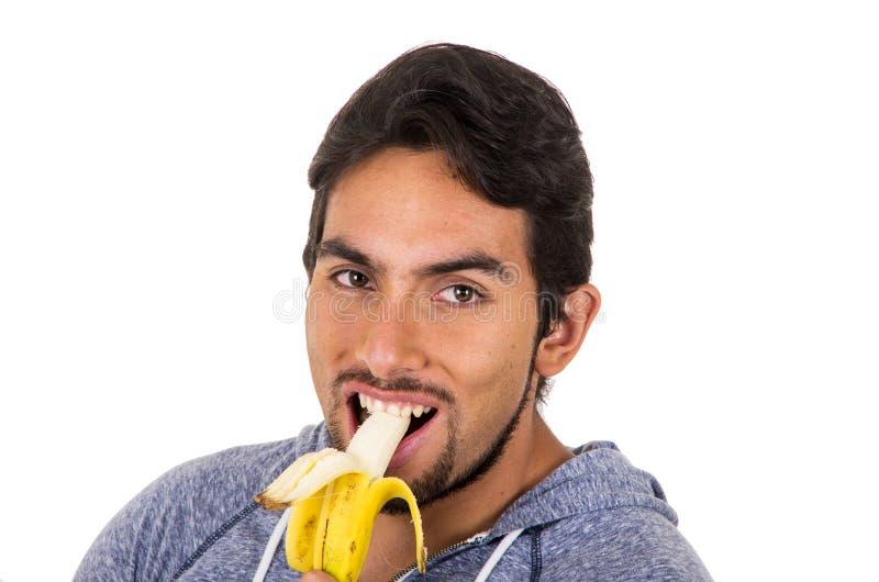 Knappe jonge mens die banaan eten stock afbeeldingen
