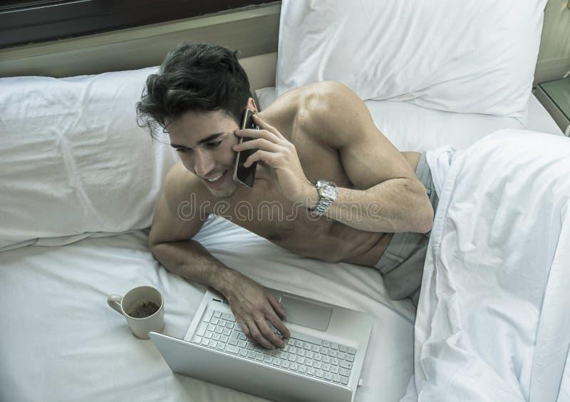 Knappe jonge mens die in bed celtelefoon uitnodigen stock afbeelding