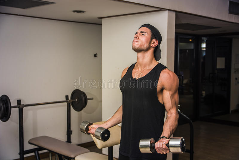 Knappe jonge mens die bicepsen in gymnastiek uitoefenen stock afbeeldingen