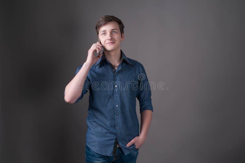 Knappe jonge mens die bij smartphone spreken, en weg op grijze achtergrond glimlachen kijken royalty-vrije stock foto