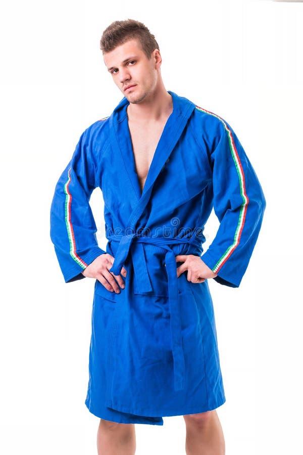 Knappe jonge mens die blauwe geïsoleerde badjas dragen, royalty-vrije stock foto's