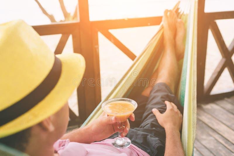 Knappe jonge mens die in een hangmat bij een zonnig strand door een oceaan liggen royalty-vrije stock foto