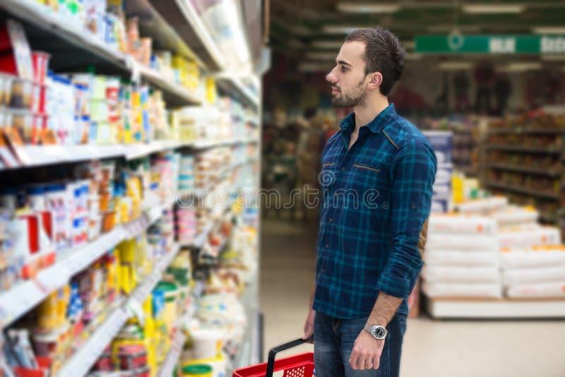 Knappe Jonge Mens die in een Kruidenierswinkelsupermarkt winkelen stock afbeeldingen