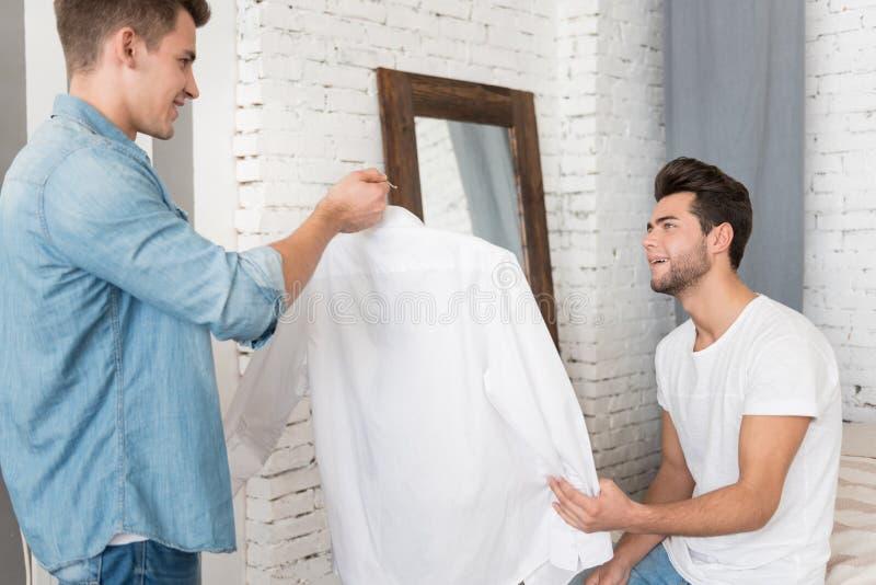 Knappe jonge mens die een overhemd geven aan zijn vriend stock foto