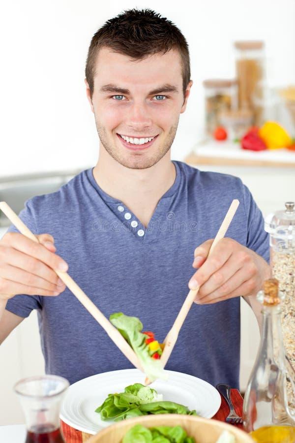 Knappe jonge mens die een salade en het glimlachen eet royalty-vrije stock afbeelding