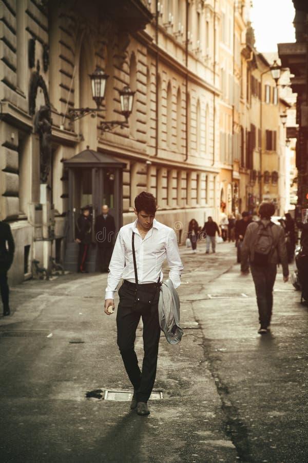 Knappe jonge mens die in Europese stadsstraat lopen royalty-vrije stock afbeelding