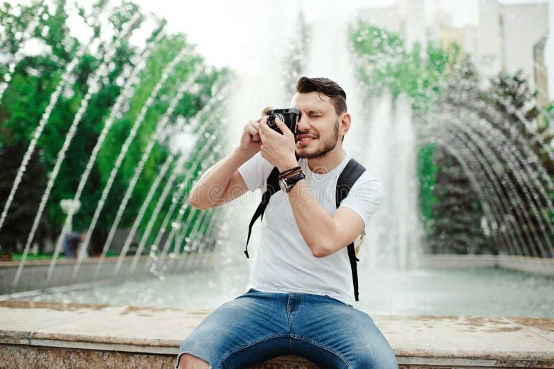Knappe jonge mens die foto in park nemen Modieuze jongen in een witte t-shirt, met bagpack die foto's nemen stock afbeeldingen