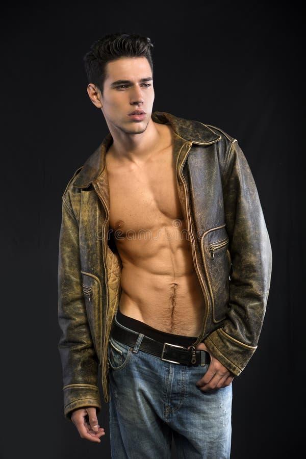 Knappe jonge mens die leerjasje op naakt torso dragen stock foto's