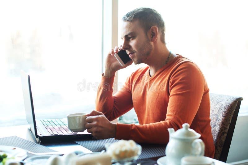 Knappe jonge mens die met notitieboekje, die aan de telefoon werken, terwijl het genieten van van koffie in koffie spreken royalty-vrije stock afbeelding