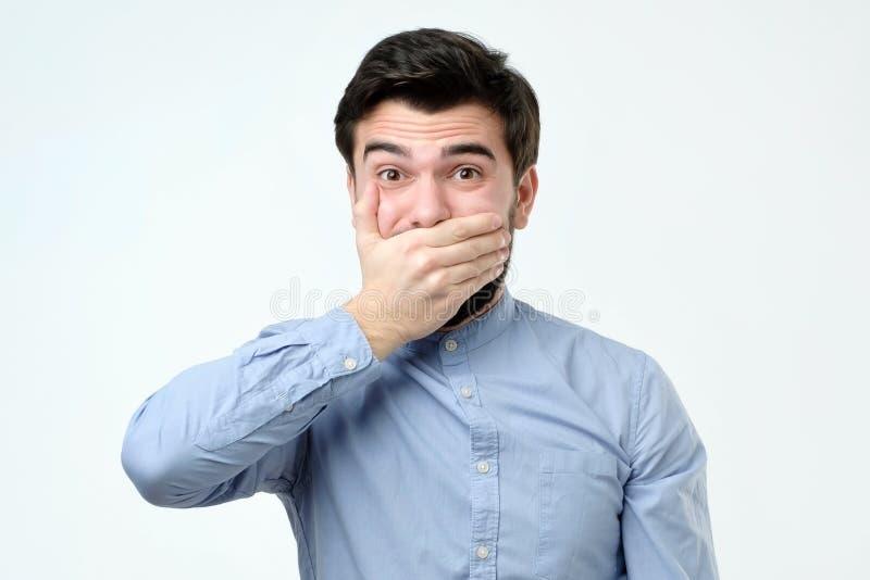 Knappe jonge mens die mond behandelen met hand en camera bekijken stock foto's