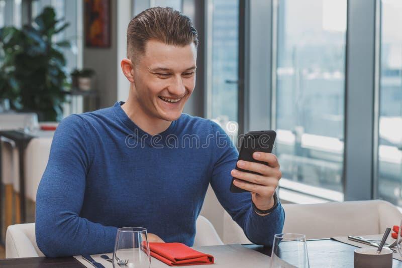 Knappe jonge mens die ontbijt hebben bij de koffie stock foto