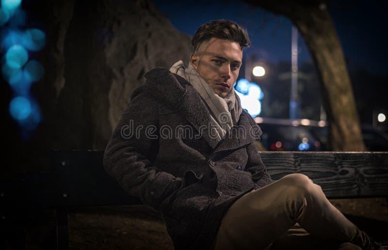 Knappe in jonge mens, die op bank bij nacht zitten royalty-vrije stock afbeelding