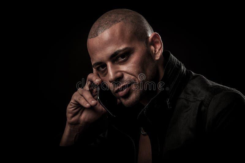 Knappe jonge mens die op celtelefoon in duisternis aan transfe spreken royalty-vrije stock afbeeldingen