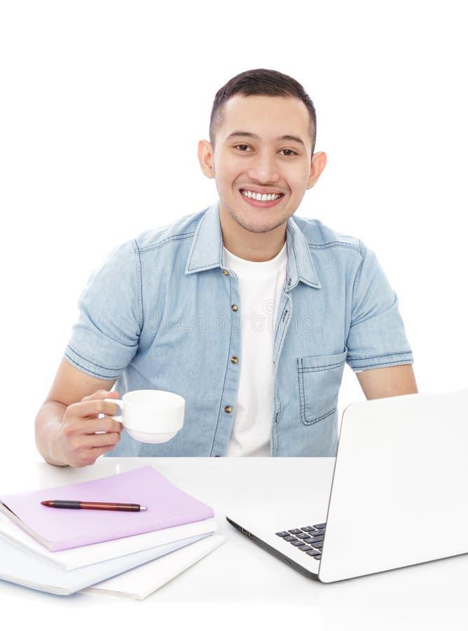 Knappe jonge mens die op laptop bestuderen terwijl het houden van een kop thee royalty-vrije stock afbeelding