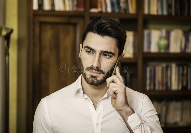 Knappe jonge mens die op telefoon thuis spreken stock foto
