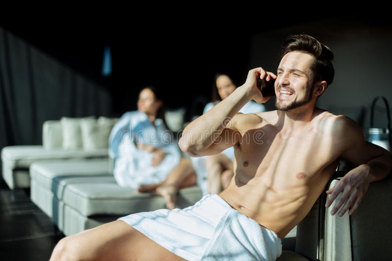 Knappe, jonge mens die op zijn celtelefoon binnen spreken in de ochtend stock fotografie