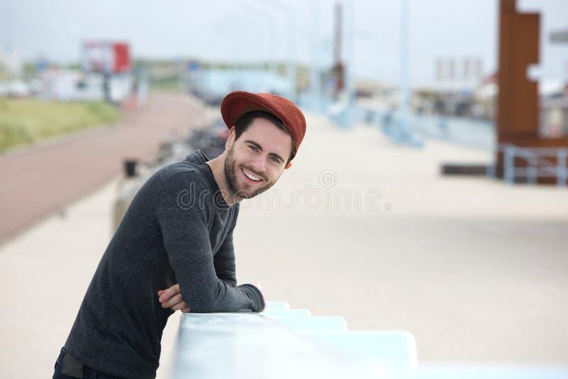 Knappe jonge mens die in openlucht glimlachen stock afbeelding