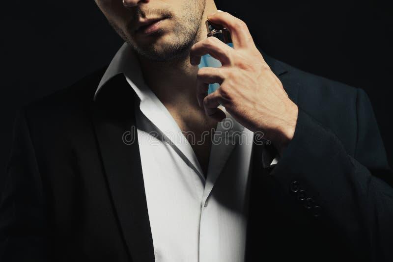 Knappe jonge mens die parfum gebruikt stock afbeeldingen