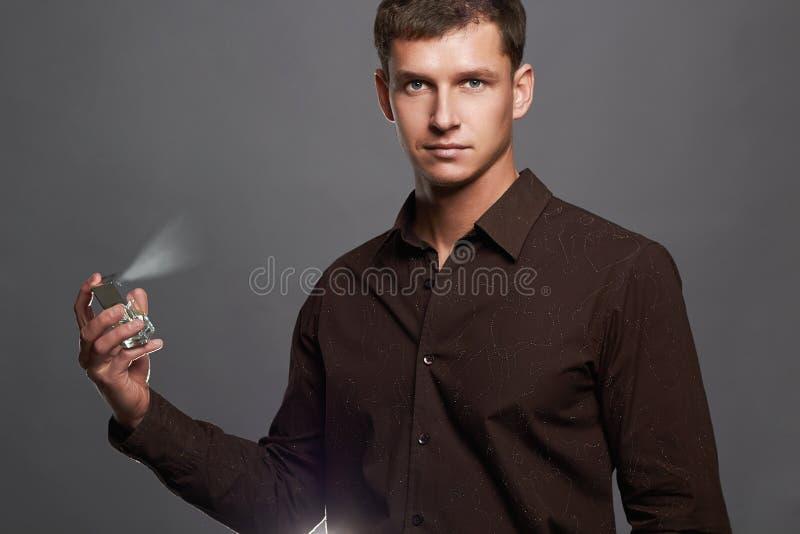 Knappe jonge mens die parfum gebruikt parfumfles en het bespuiten geur stock fotografie