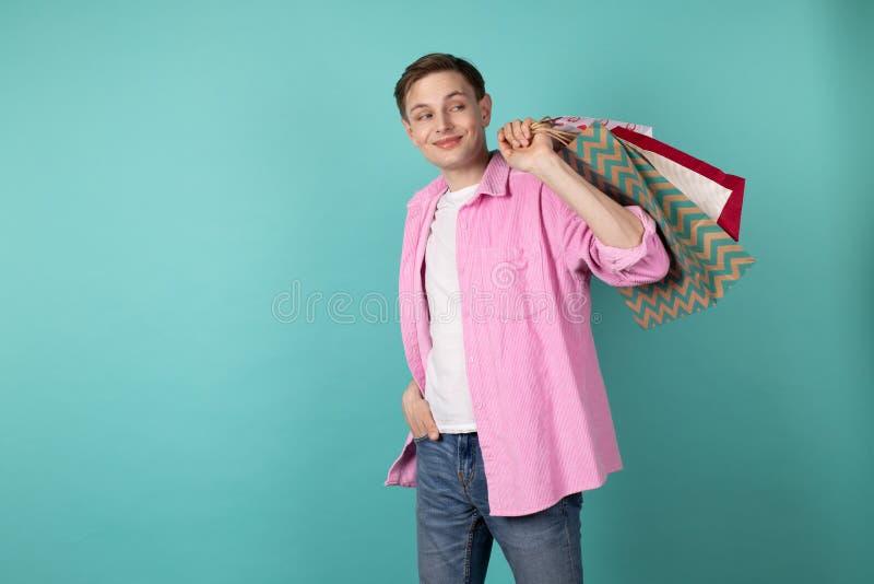 Knappe jonge mens die in roze overhemd kleurrijke shoping zakken op de schouder houden royalty-vrije stock foto