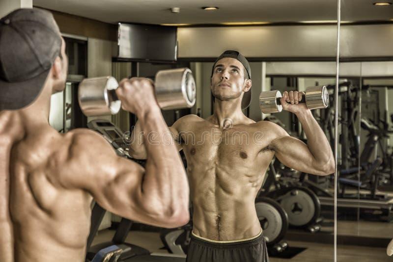 Knappe jonge mens die schouders in gymnastiek uitoefenen stock foto's