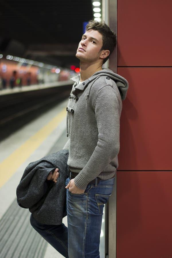 Knappe jonge mens die tegen muur zich aan de gang of metropost bevinden stock foto