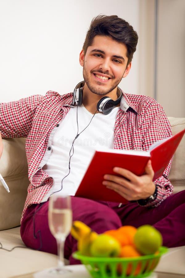 Knappe jonge mens die thuis op notitieboekje, het zitten schrijven stock foto's