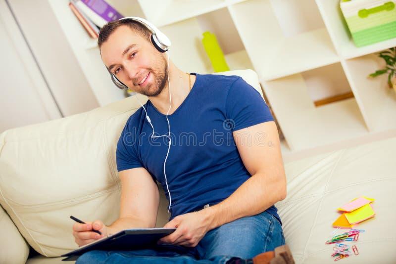 Knappe jonge mens die thuis op notitieboekje schrijven, die op laag zitten royalty-vrije stock foto