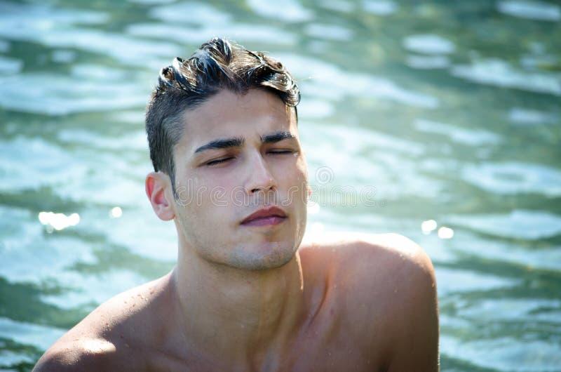 Knappe jonge mens die uit water komen stock afbeeldingen
