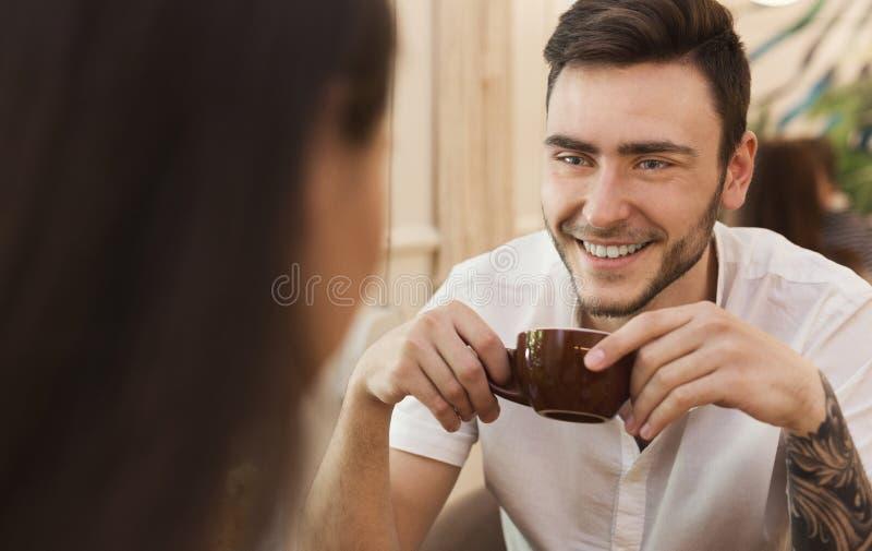 Knappe jonge mens die van koffie in een koffie genieten stock foto