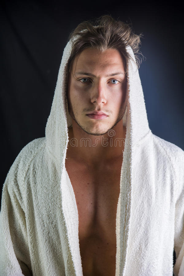 Knappe jonge mens die witte badjas dragen royalty-vrije stock afbeeldingen