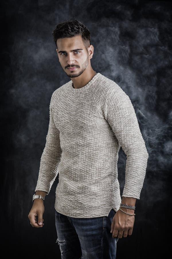 Knappe jonge mens die witte sweater dragen stock foto's