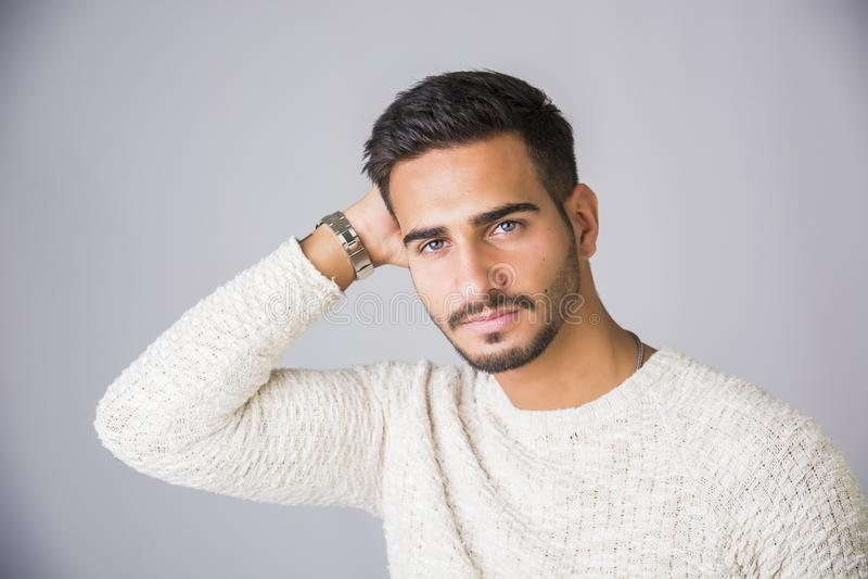 Knappe jonge mens die witte sweater in studio dragen royalty-vrije stock fotografie